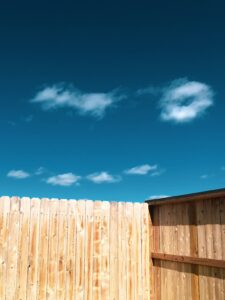 Wooden Houston fence against sky helps separate two neighboring properties.