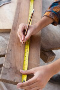 employee from Houston fence company measuring wood for fence board